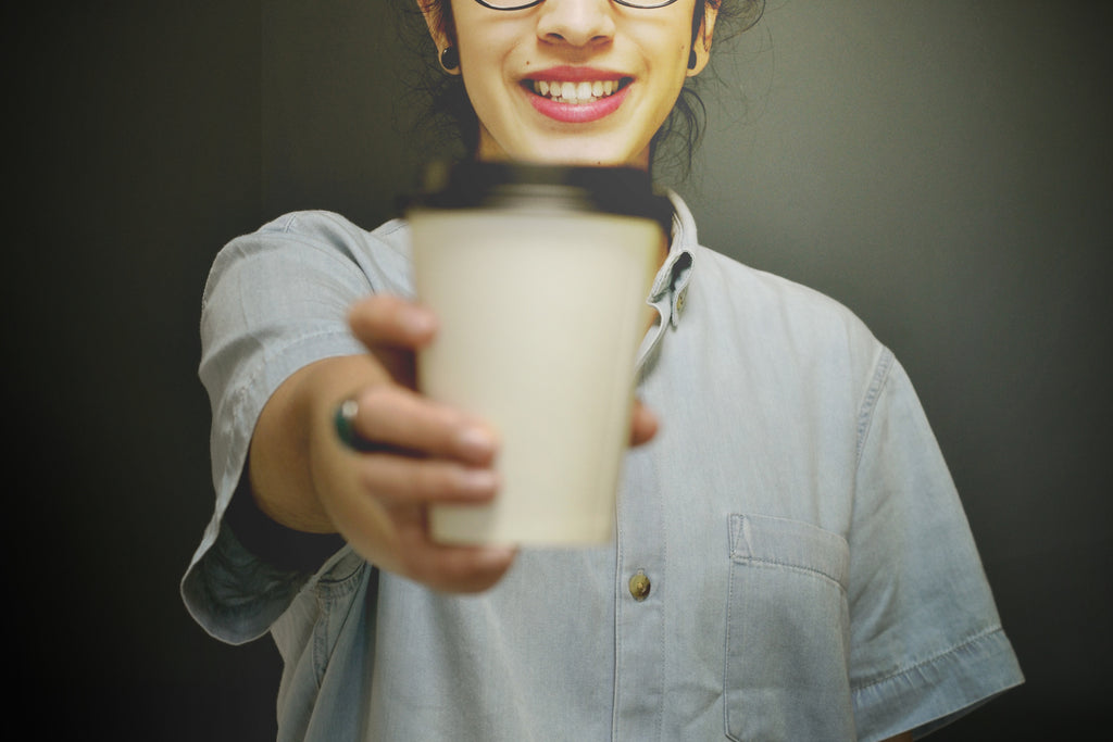 A young woman holding a paper cup of coffee in front of her.