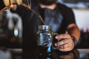A specialty coffee class, training in Chicago and Chicagoland. A barista pouring a cold brew coffee into a mason jar.