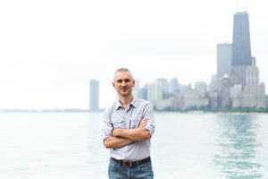 The founder of Black Fodder Coffee Co. Maciej Wolfart standing with arms crossed at a beach in Chicago.