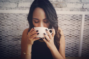 A young woman savoring a cup of coffee.