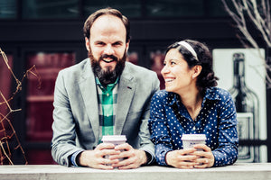 A happy engaged couple enjoying specialty coffee by the river downtown Chicago.