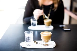 A cortado coffee with latte art served with carbonated water, a woman in the background.