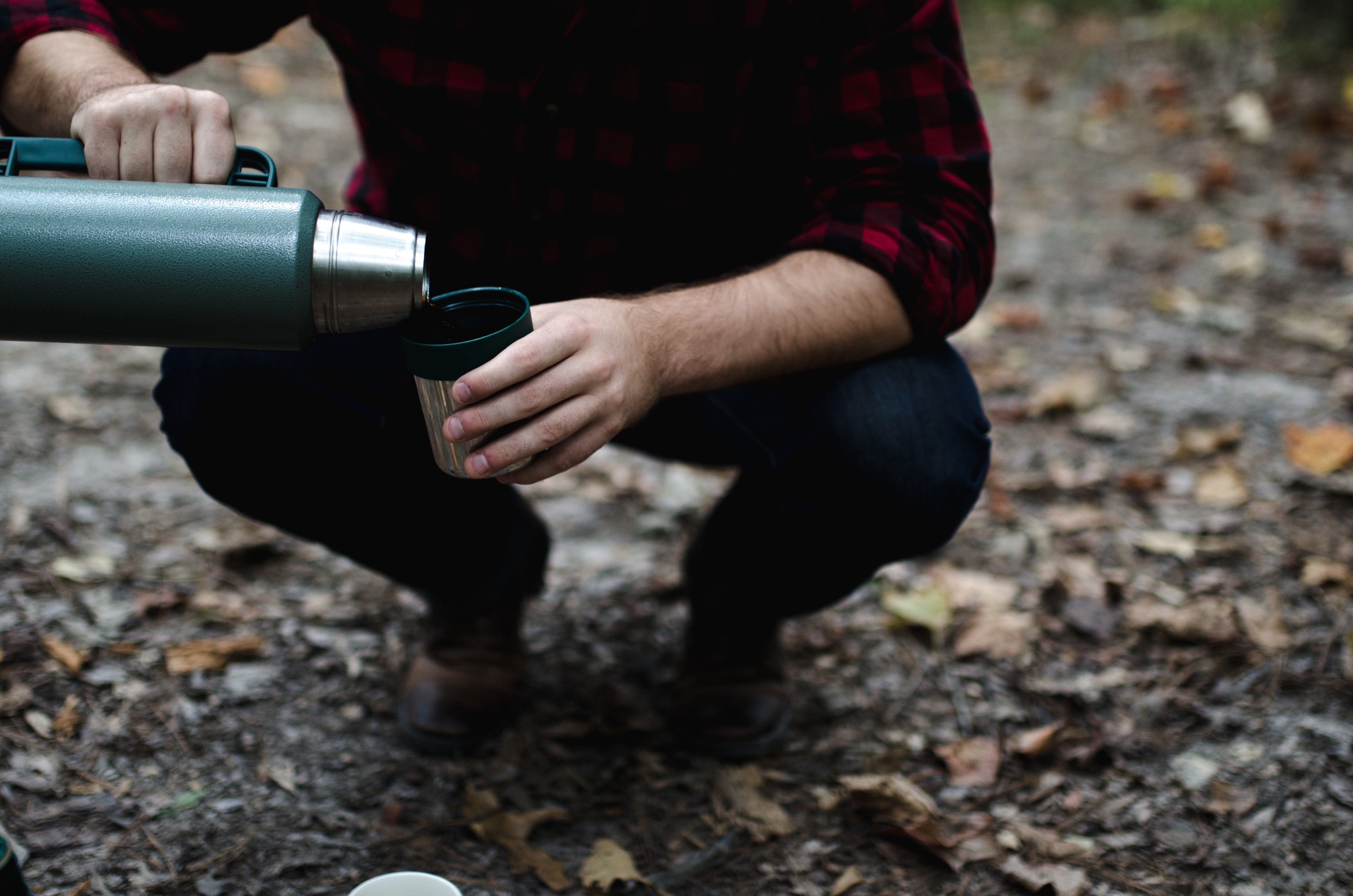 A person pouring coffee from a thermos into a cup.