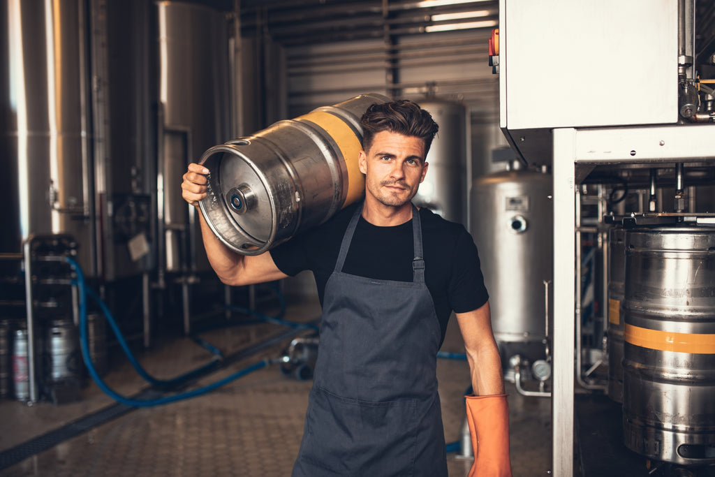 A young brewer carrying a keg of small-batch craft cold brew, nitro coffee, tea, or kombucha.