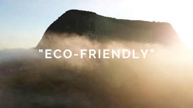 A misty morning image of a mountain that is a previously undiscovered rainforest in Mozambique's Zambezia province.  The word eco-friendly appears over the rainforest in quotes because the post is about the authors dislike of the term eco-friendly.