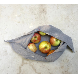 Gray cotton bento bag with long tie-able ends lays open on a marble countertop with reddish, yellow apples inside.