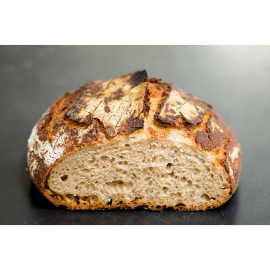 A crusty loaf of sourdough bread with a slice cut out of it sits on a countertop.