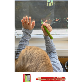 Toddler drawing flowers on window with Stabilo washable markers.
