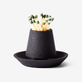 Black match striker holding wood matches with green tips inside.