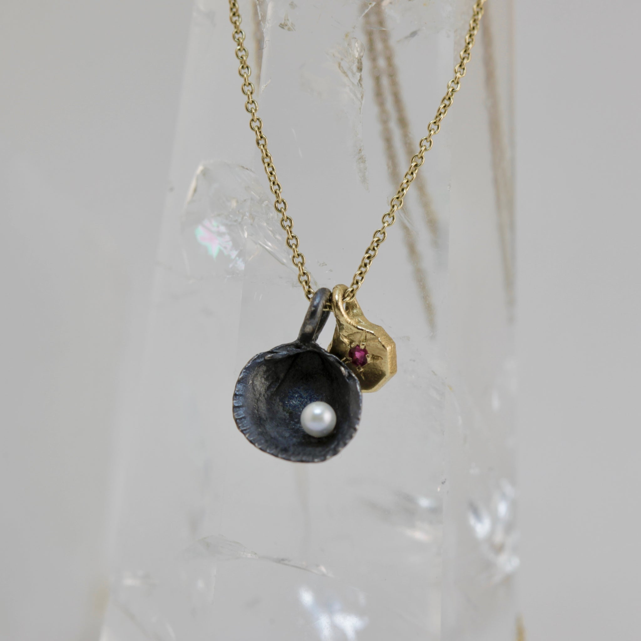 Midnight Siren Pendant, oxidised black shell with pearl, 9ct gold charm with ruby