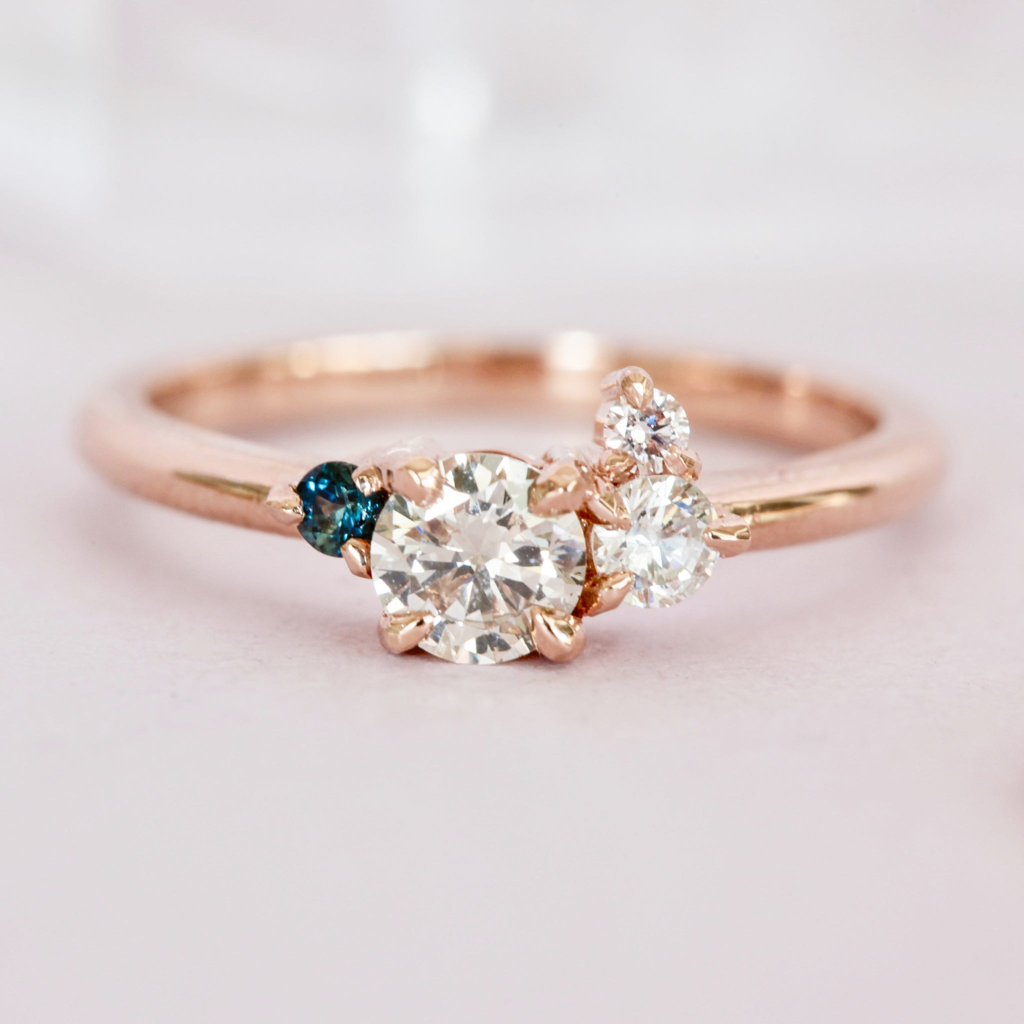 bespoke handmade engagement ring in 18ct rose gold, claw set ethically sourced Australian sapphire, large  white and champagne diamonds