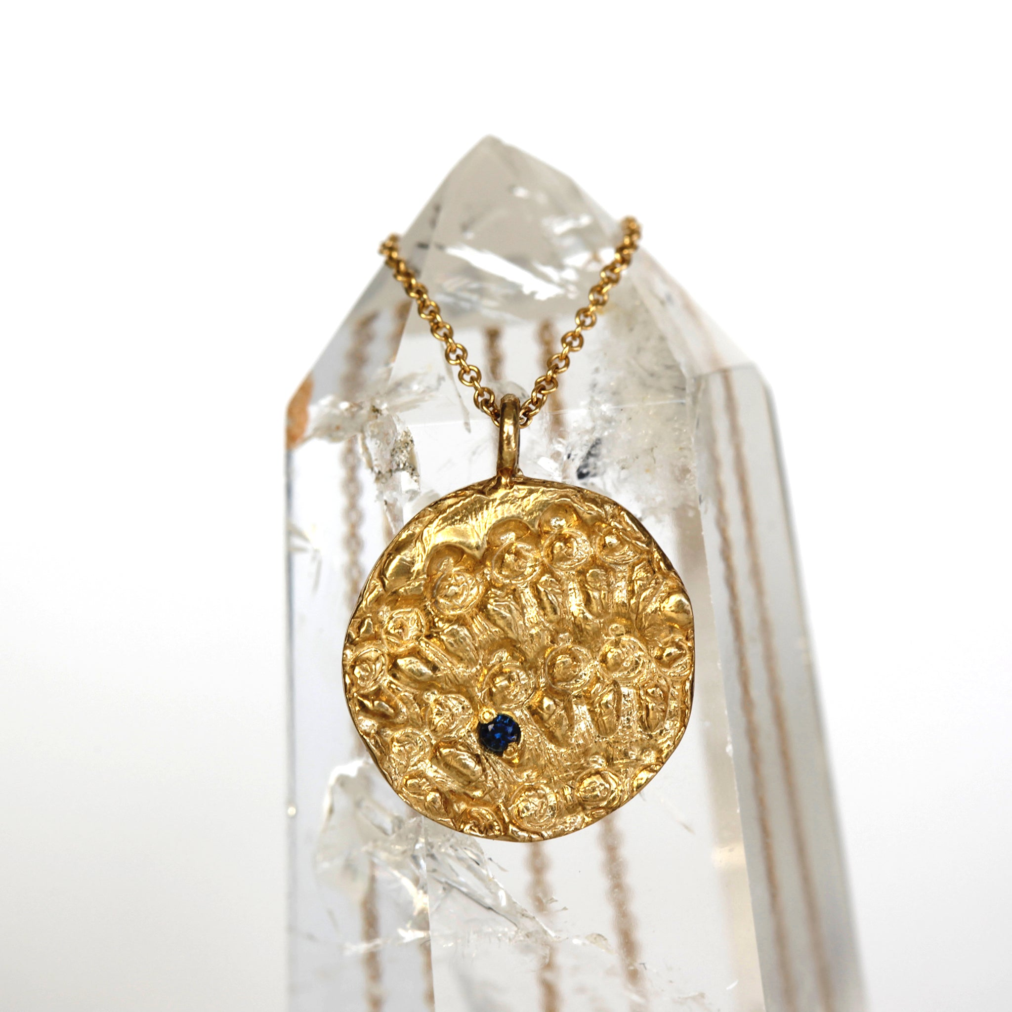 Gold textured pendant with sapphire