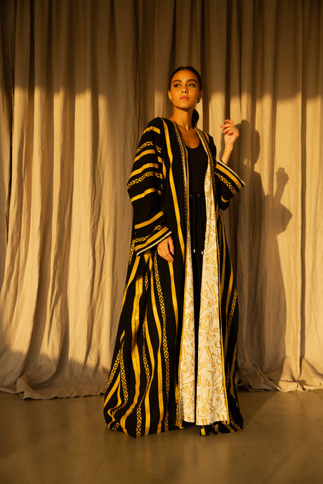 a silk long over garment in black and gold