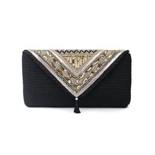 The front of a hand-embroidered black crochet clutch, ornamented with traditional lead beads and gold and silver sequin, adorned with a silk black tassel.