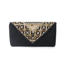 The back of a hand-embroidered black crochet clutch, ornamented with traditional lead beads and gold and silver sequin, adorned with a silk black tassel.