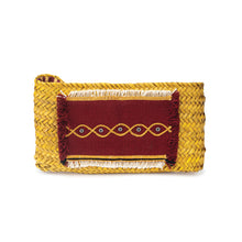 Front view of a naturally-dyed (yellow) hand-woven palm frond clutch with an original traditional hand-embroidered Sadu piece