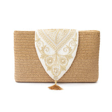 Front view of a white crochet clutch with a traditional Najdi design embroidered in gold thread and pearls on the flap, and adorned with a silk tassel