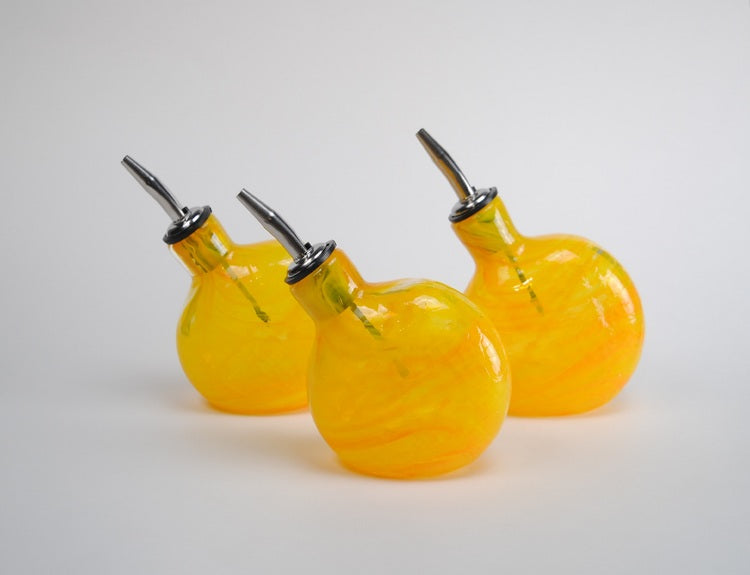 A set of three bright yellow handmade glass oil bottles