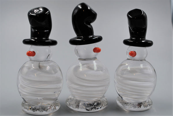 A group of three snowman figures with slight variation in each. All have black top hats and small orange noses.