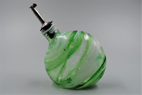 A single handmade glass oil bottle, colored with green, clear, and white swirls, shown with the spout facing to the left.