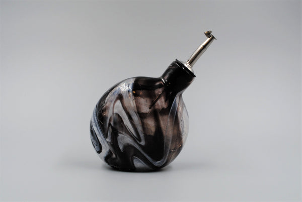 A single black and white oil bottle, turned to the right, with stainless steel spout. The black and white glass is swirled through the body of the oil bottle.
