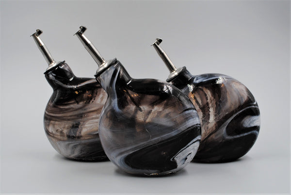 A group of three black and white oil bottles, each slightly different in form and size.