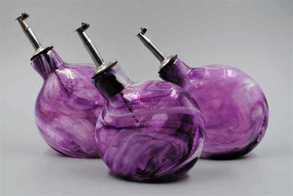 A group of purple glass oil bottles, all slightly different in size and shape.