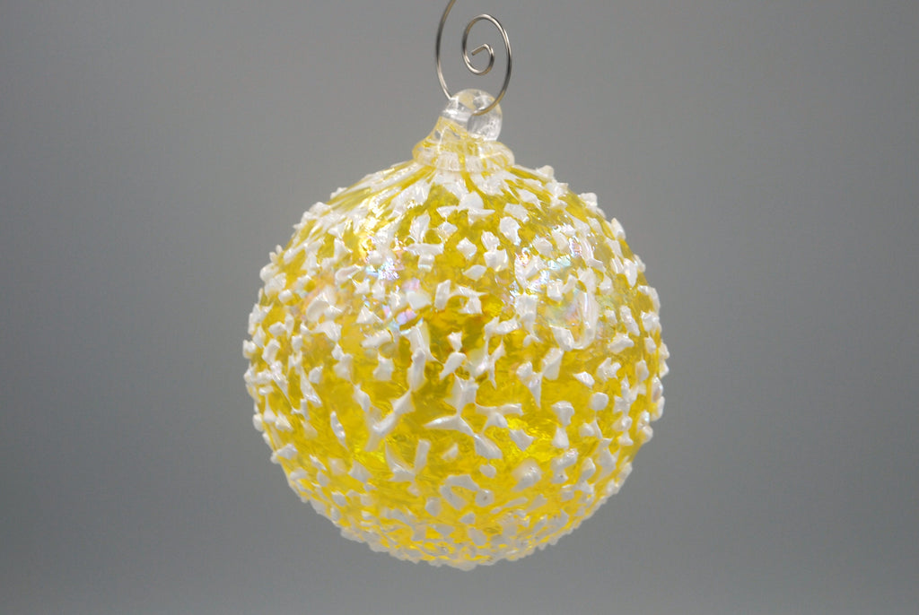 One yellow blizzard ornament hanging from an ornament hook
