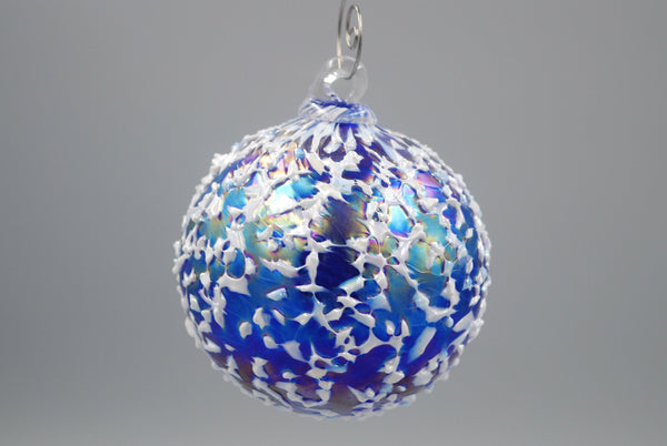 One cobalt blue blizzard ornament hanging from an ornament hook