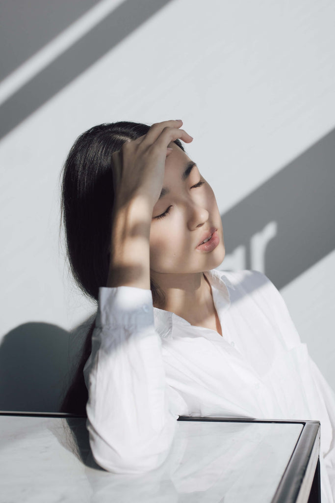 woman leaning on a white table holding her forehead