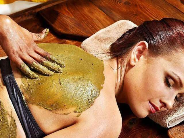 woman being massaged on the back while lying down using Ayurvedic powder