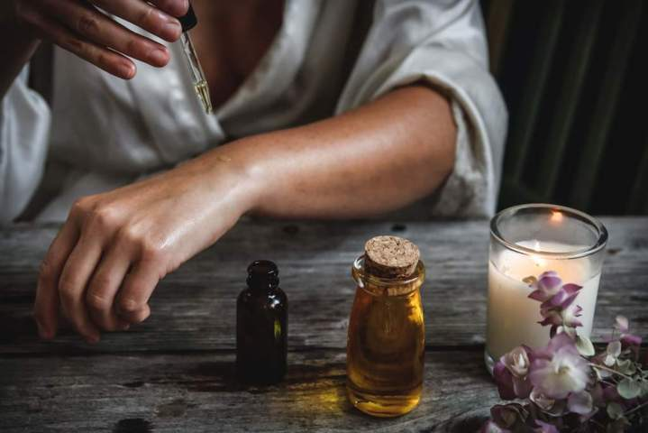 woman dropping essential oil on arm and bottles of oil on the table