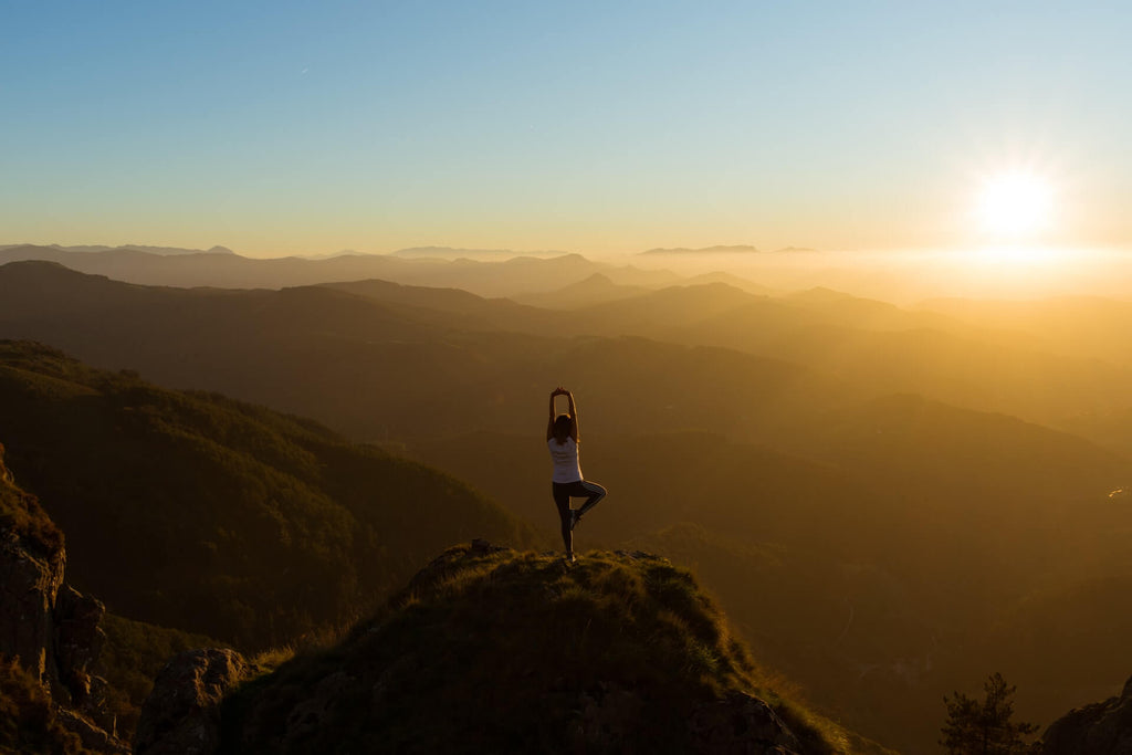 woman standing on a hill landscape doing a yoga pose