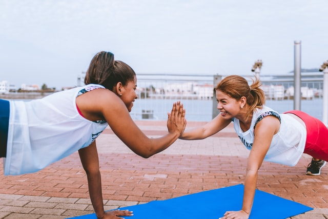 two women doing a couple yoga pose outdoors