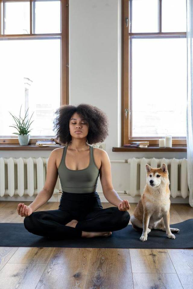 woman doing yoga lotus pose with a dog beside her