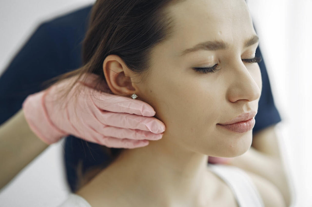 woman being massaged along the jawline looking relaxed