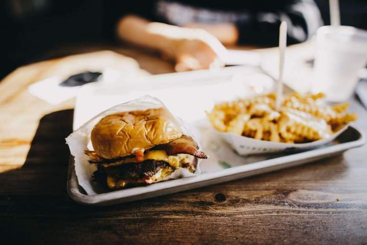 plate containing fries and bacon burger