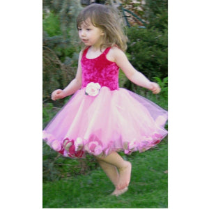 girl running through grass in pink fairy dress