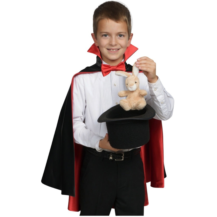 boy wearing magician cape and pulling rabbit out of a hat