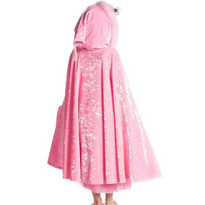 girl wearing pink velvet hooded cape standing with back to camera