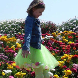 girl wearing green tulle fairy tutu in a field of flowers