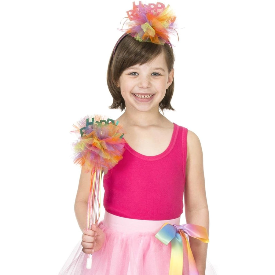 Girl wearing happy birthday headband and pom pom wand