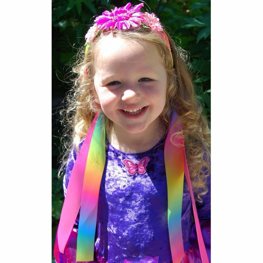 girl wearing rainbow ribbon headband and purple fairy wings