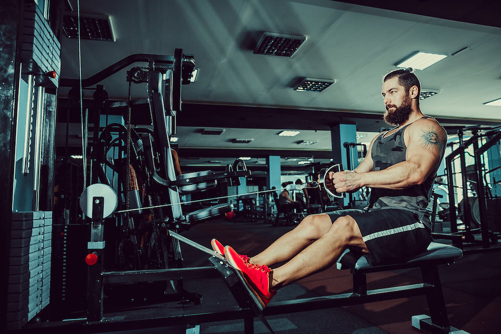 Man working back muscles using cable row machine in gym