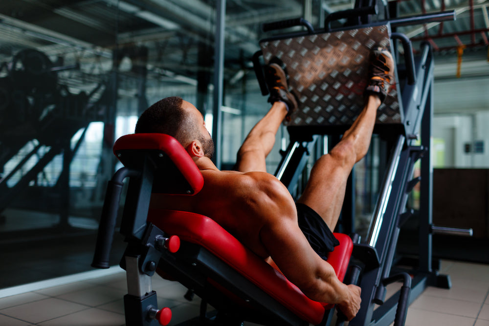 Man working leg muscles using leg press machine in gym