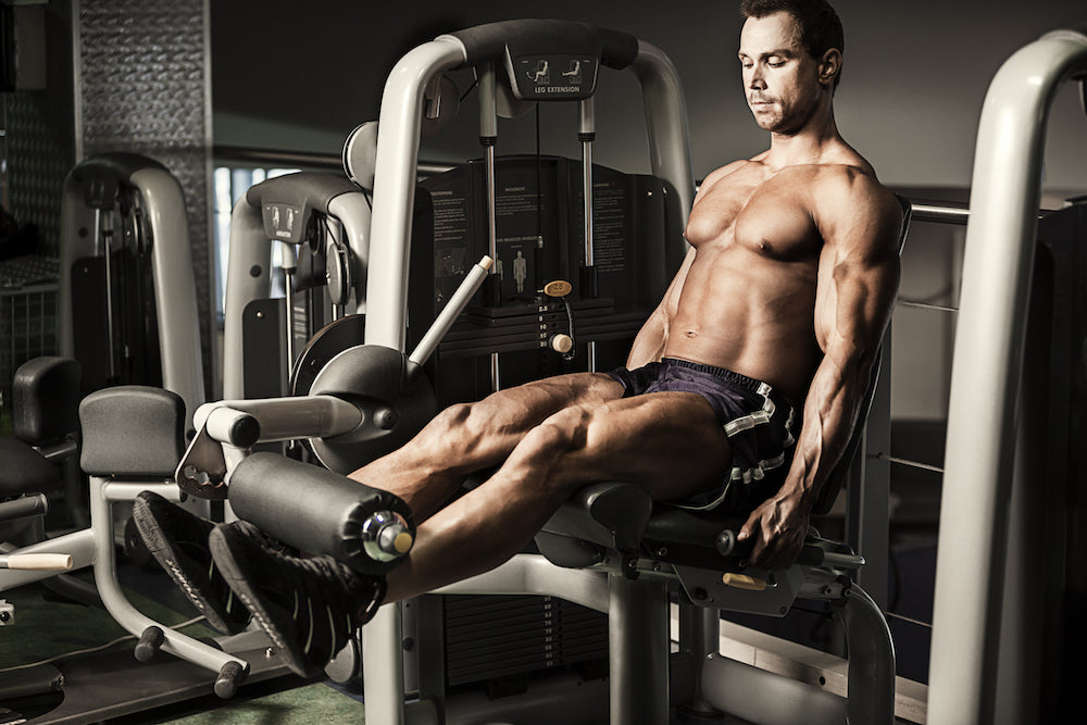 Man working leg muscles using leg extension machine in gym