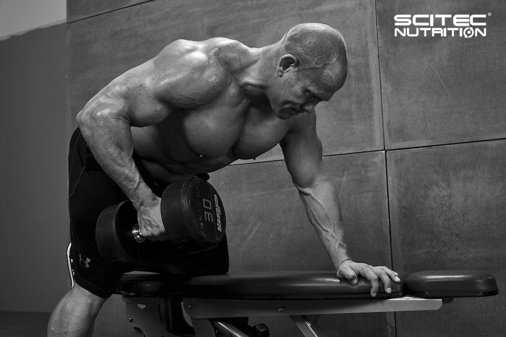 Scitec model lifting dumbbell on workout bench