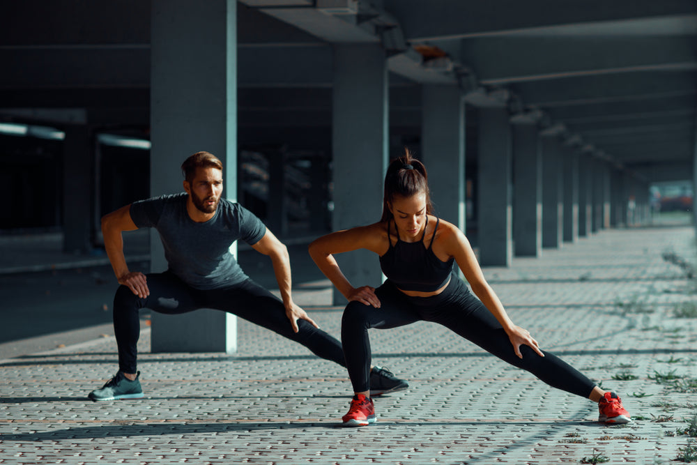 Man and woman performing stretches before workout