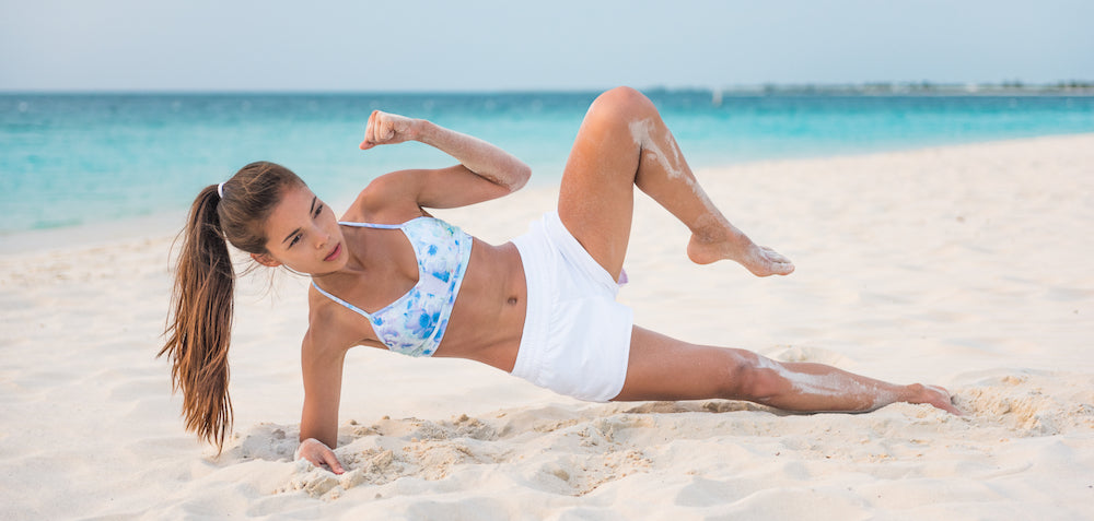 Woman performing side plank crunch on beach