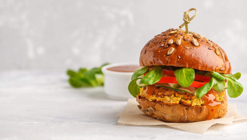 Veggie burger made with protein powder on a bun with tomatoes and greens